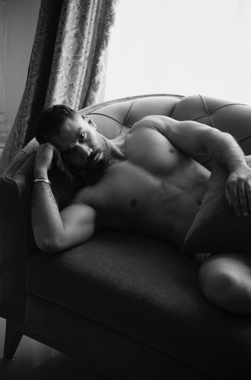 Black and white photo of a solemn looking mxn, lying on a couch, staring into the camera. Hx is shirtless, with a metallic bracelet on one wrist. Hx looks strong, and holds a pillow over his lap.