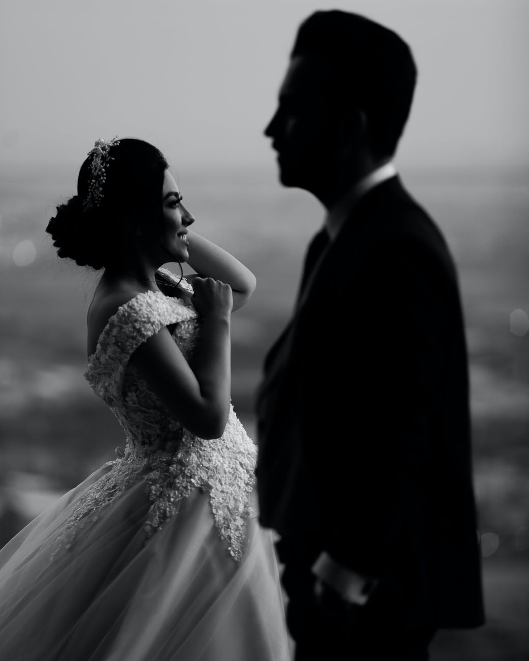 Black and white image of a bride, smiling. In the foreground is a blurry silhouette of the groom.