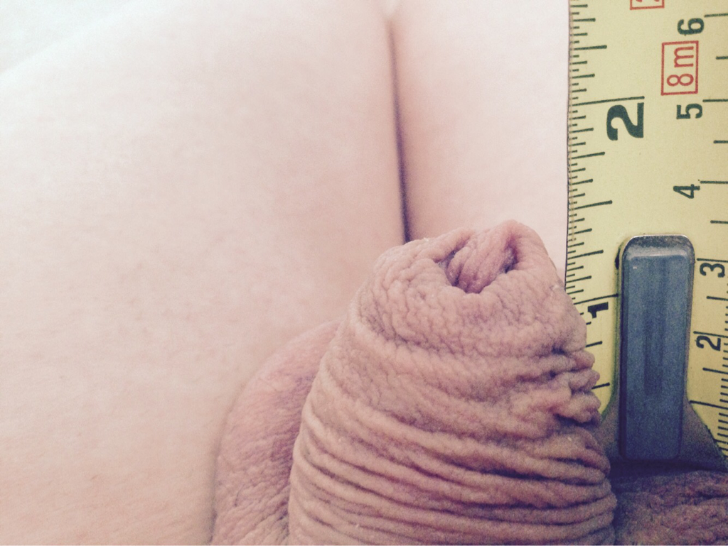 NSFW. A measuring tape is held up against a flaccid penis. The measuring tape shows less than 2 inches.