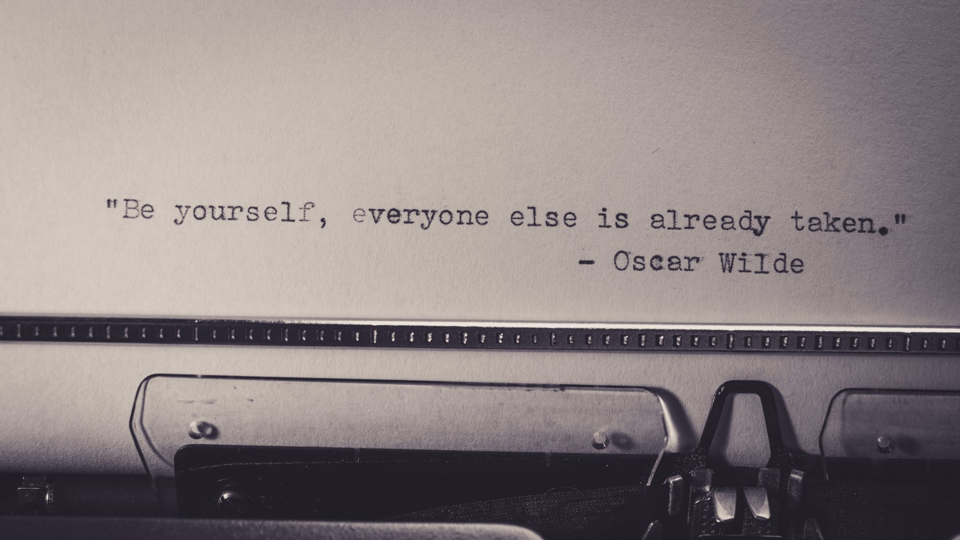 """Black and white image of a piece of paper in a typewriter. The paper says, """"be yourself, everyone else is already taken,"""" a quote by Oscar Wilde."""
