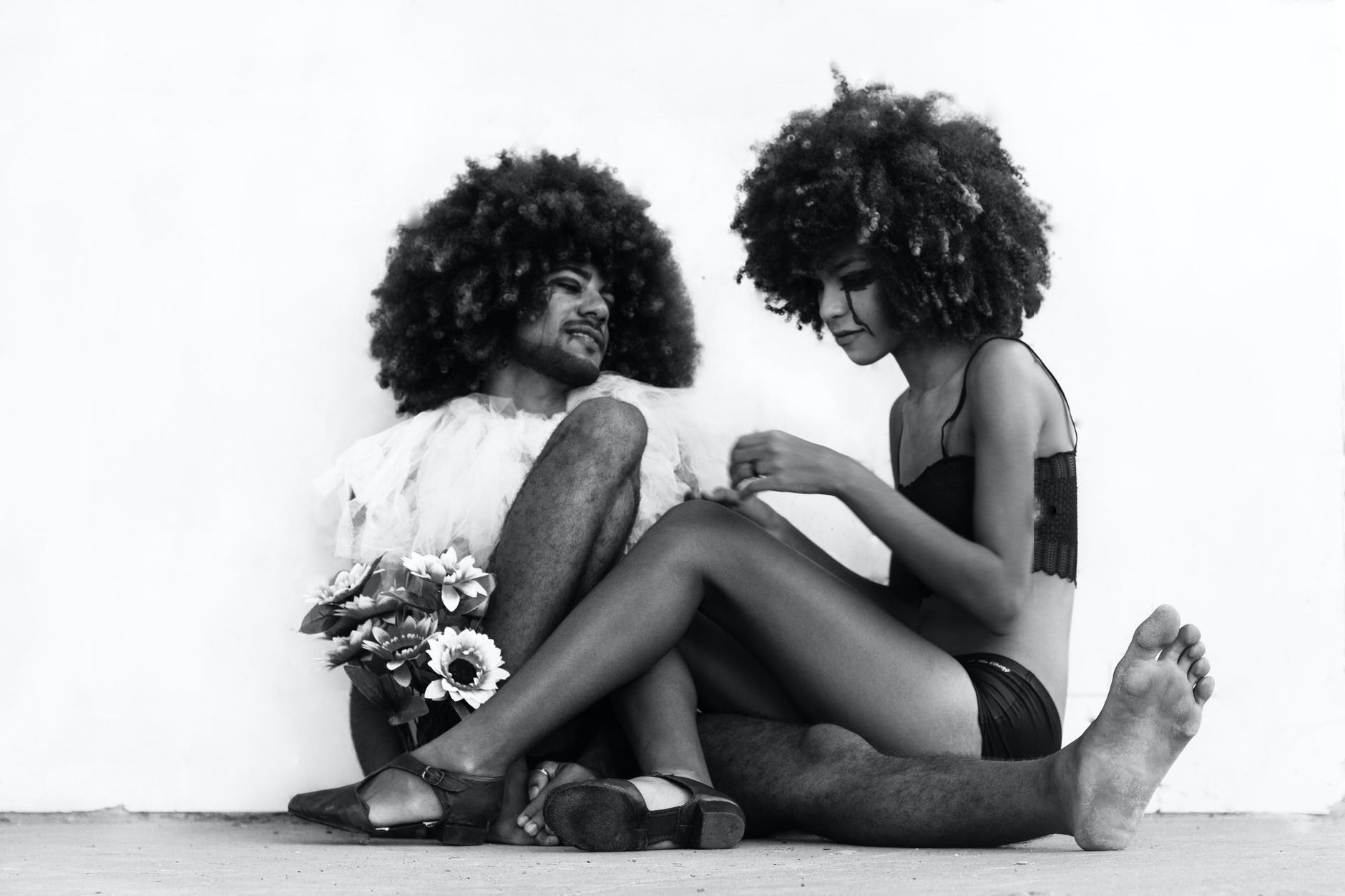 Black and white artistic photo of a couple sitting on the ground. The womxn's legs hang over the mxn's legs, as he leans against a white wall. They both have black makeup running down their face like tears, and yet, they smile. The womxn plays with the veil that is around the mxn's neck, and he holds flowers in his right hand.