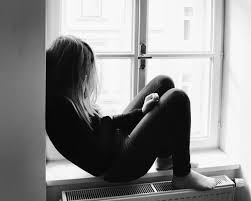 Black and white image of a womxn sitting hunched on a windowsill. She is in a black sweater, and her hair covers her face. It is melancholic.