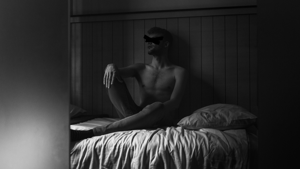 """Black and white photo, camera's perspective is peering through the door, and we see a shirtless mxn on a bed, an """"X"""" over his eyes. He looks thoughtful, staring off to the right."""