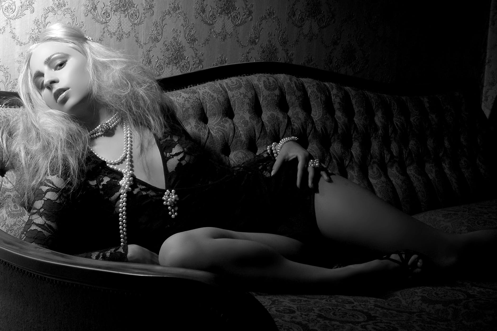 Black and white image of a womxn lying on a tufted, chaise lounge. Hxr hair  is white blonde, and has pearls hanging from her neck. Shx's wearing black lace and stares at the camera seductively.